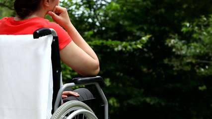 Depressed woman sitting on wheelchair in garden movie