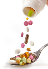 various pills falling into spoon