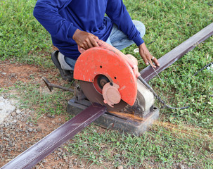 Worker cutting metal with cutting machine