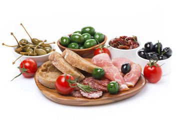 deli meats, pickles and olives on a wooden board, isolated