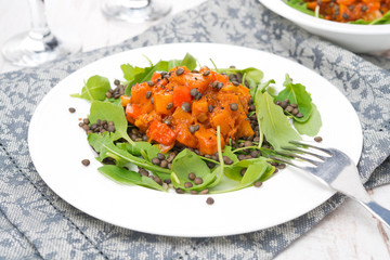 salad with arugula, black lentils and vegetable stew on plate