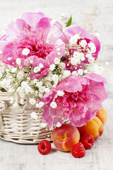 Basket of pretty pink peonies, white rustic background
