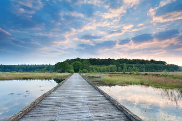 wooden path on lake water at sunrise