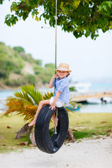 Little girl on tire swing