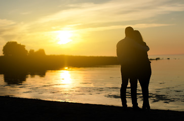 Young couple enjoying the sunset. Two silhouettes.