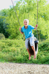 Happy school boy swinging  at playground sitting on old tire