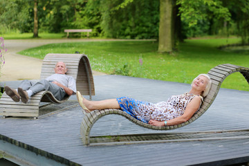 Senior couple relaxing on wooden chairs in summer park