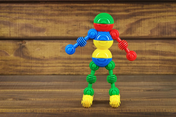 Toy robot made from toy plastic colorful details on wooden backg