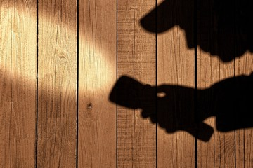Male silhouete with serchlight on wooden wall