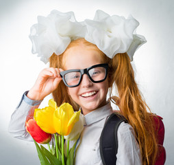 Schoolgirl with backpack and flowers
