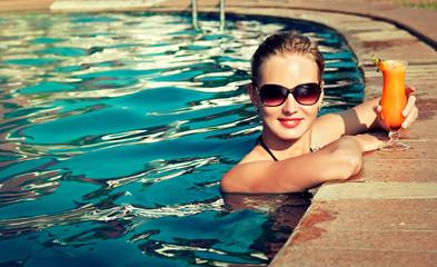 Beautiful girl rests near the swimming pool , sunbathing.