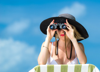 Beautiful woman in bikini looking through binoculars