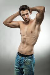 Handsome muscular man posing half naked