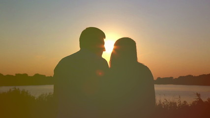 Young couple in love at sunset on the lake. Enjoying each other