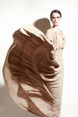 Elegant woman in flying dress. Fashion model in long dress