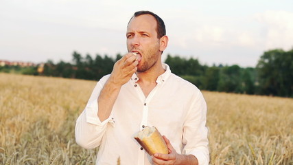 Man eating bread in wheat field, super slow motion, 240fps