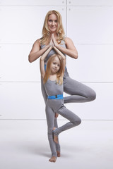 Mother and daughter doing yoga exercise, fitness, gym