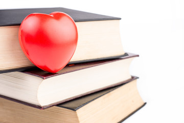 Books with heart on white isolated background