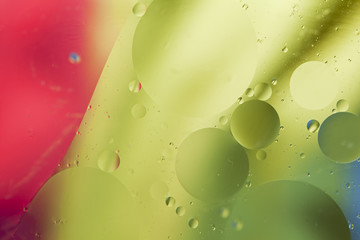 Abstract pattern of colored oil bubbles on water