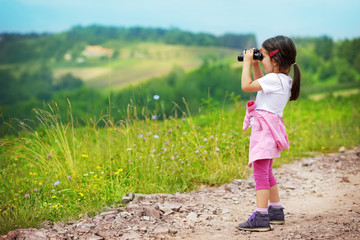 Little girl looking through binoculars outdoor. She is lost