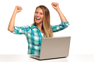 Happy  woman using laptop seated at the desk