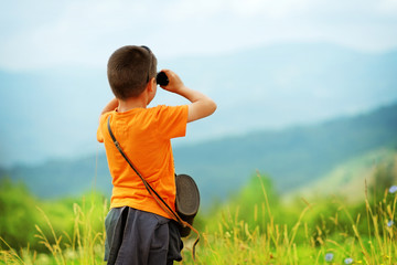 Little boy looking through binoculars outdoor. He is lost