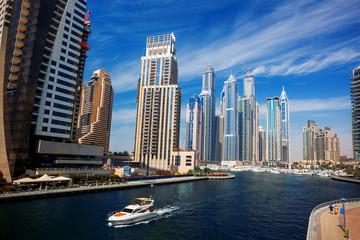 Dubai Marina with boat against skyscrapers in Dubai, UAE