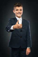 boy in black suit showing thumbs up