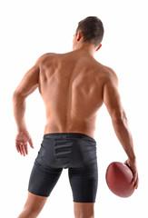 Musculoso jugador de rugbi sujetando un balon.