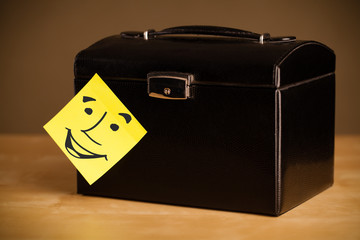 Post-it note with smiley face sticked on a box
