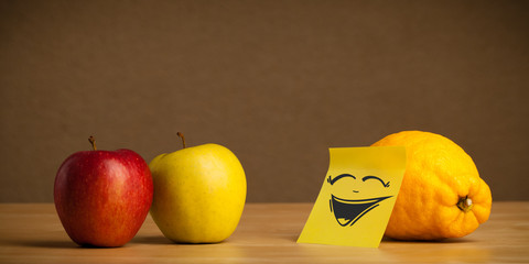 Lemon with post-it note laughing on apples