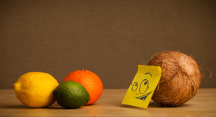 Coconut with post-it note looking curiously at citrus fruits