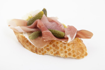 Spanish food tapas.Toast with prosciutto and small gherkins
