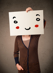 Woman holding a cardboard with a smiley face on it