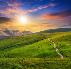 road through a meadow in high mountains at sunset