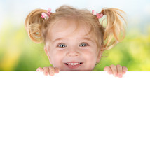 Smiling little girl peeking behind a board