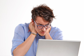Hombre joven preocupado trabajando en un ordenador portátil.