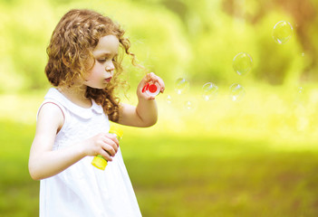 Cute curly little girl blowing soap bubbles outdoors summer