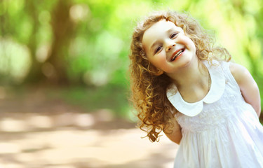 Cute baby girl shone with happiness, curly hair, charming smile,