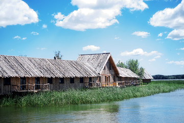 Wooden house on the bank of the river, summer season