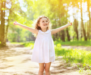 Positive charming curly little girl enjoying summer sunny day