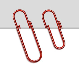 Red metal paperclip and paper