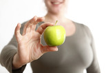 Woman holds a green apple into to camera