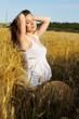Happy pregnant woman portrait in a wheat field.
