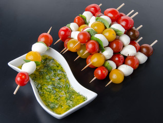 Cherry tomatoes and mozzarella on skewers and a vinaigrette sauc