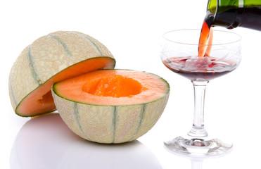 Glass of porto wine with a melon cut in half
