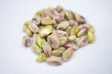 A heap of pistachio nuts on a white background on a sunny day.