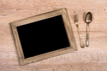 Tafel mit Rahmen aus Holz und Gabel und Löffel