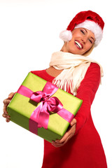Happy girl showing a gift wearing santa claus hat
