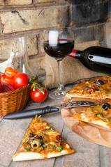Pizza with wine and some ingredients on a firebricks background